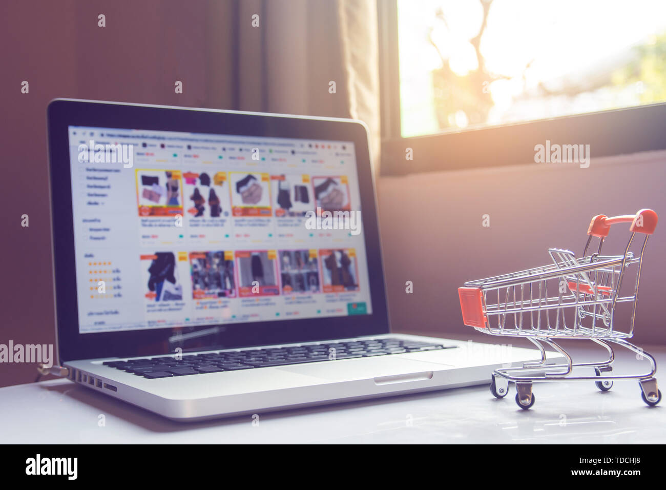 Shopping online concept - Empty shopping cart or trolley and laptop on white table. Shopping service on The online web. with copy space Stock Photo