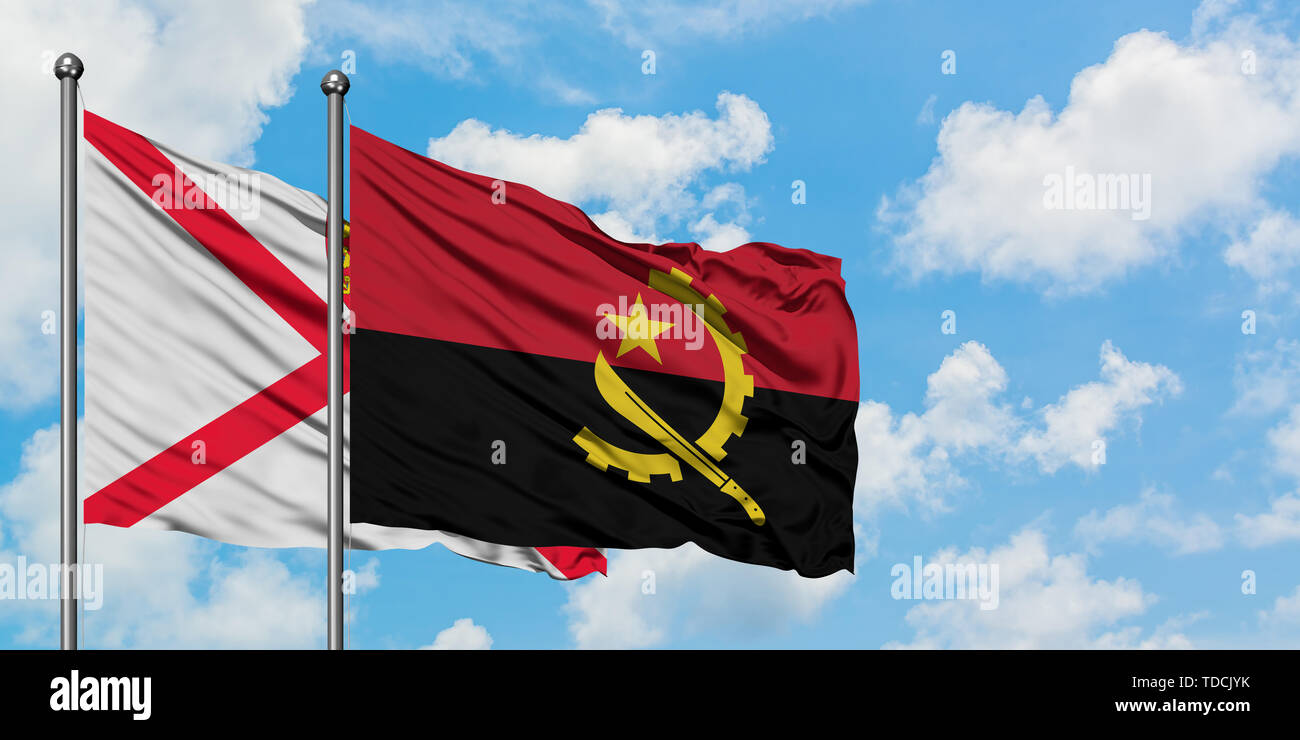 Jersey and Angola flag waving in the wind against white cloudy blue sky together. Diplomacy concept, international relations. - Stock Image