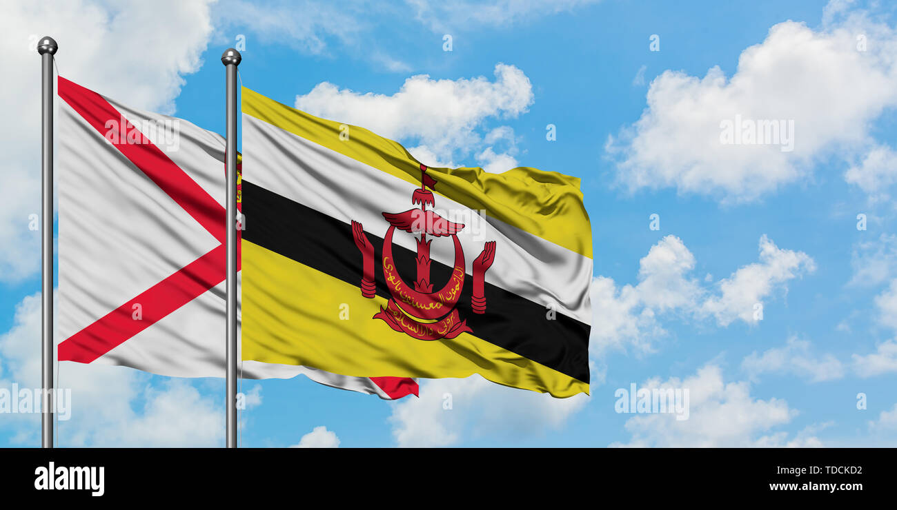 Jersey and Brunei flag waving in the wind against white cloudy blue sky together. Diplomacy concept, international relations. - Stock Image