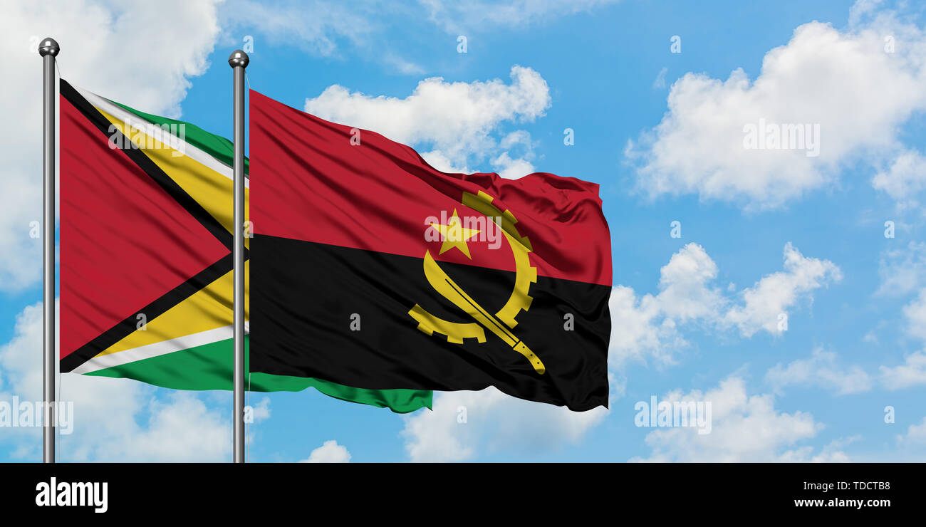Guyana and Angola flag waving in the wind against white cloudy blue sky together. Diplomacy concept, international relations. - Stock Image
