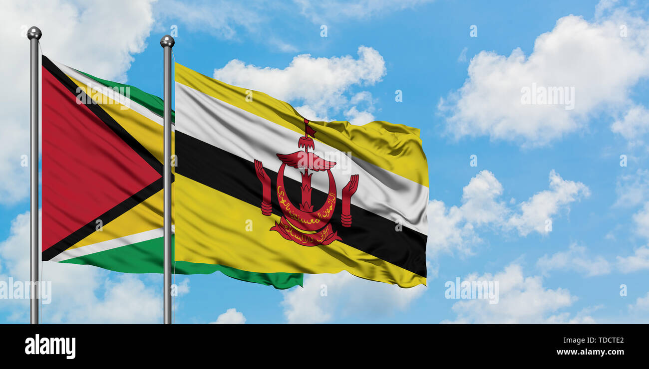 Guyana and Brunei flag waving in the wind against white cloudy blue sky together. Diplomacy concept, international relations. - Stock Image