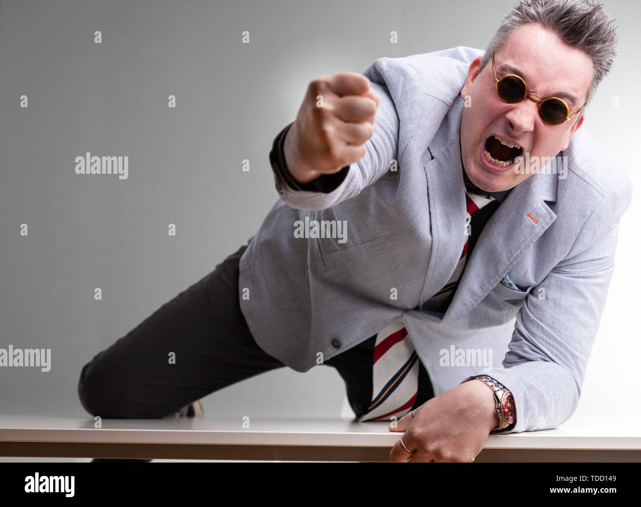 Furious belligerent man punching towards the camera leaning across the table in a show of aggression and domination - Stock Image