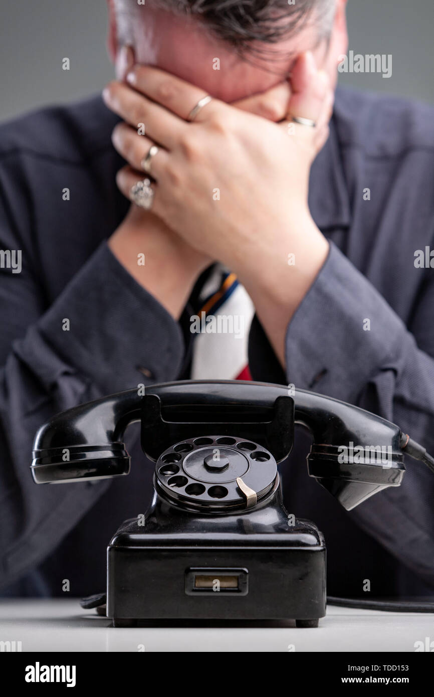 Despondent man covering his eyes with his hands and bowing his head in hopelessness after receiving bad news on the telephone in the foreground - Stock Image