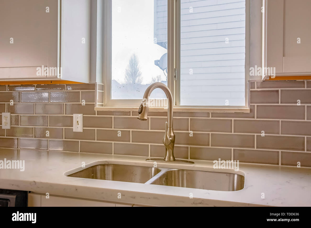 Double Sink And Faucet Of A Kitchen With View Outdoors Through The Window Glossy Tiles On Wall Can Be Seen Below Hanging Wooden Cabinets Stock Photo Alamy