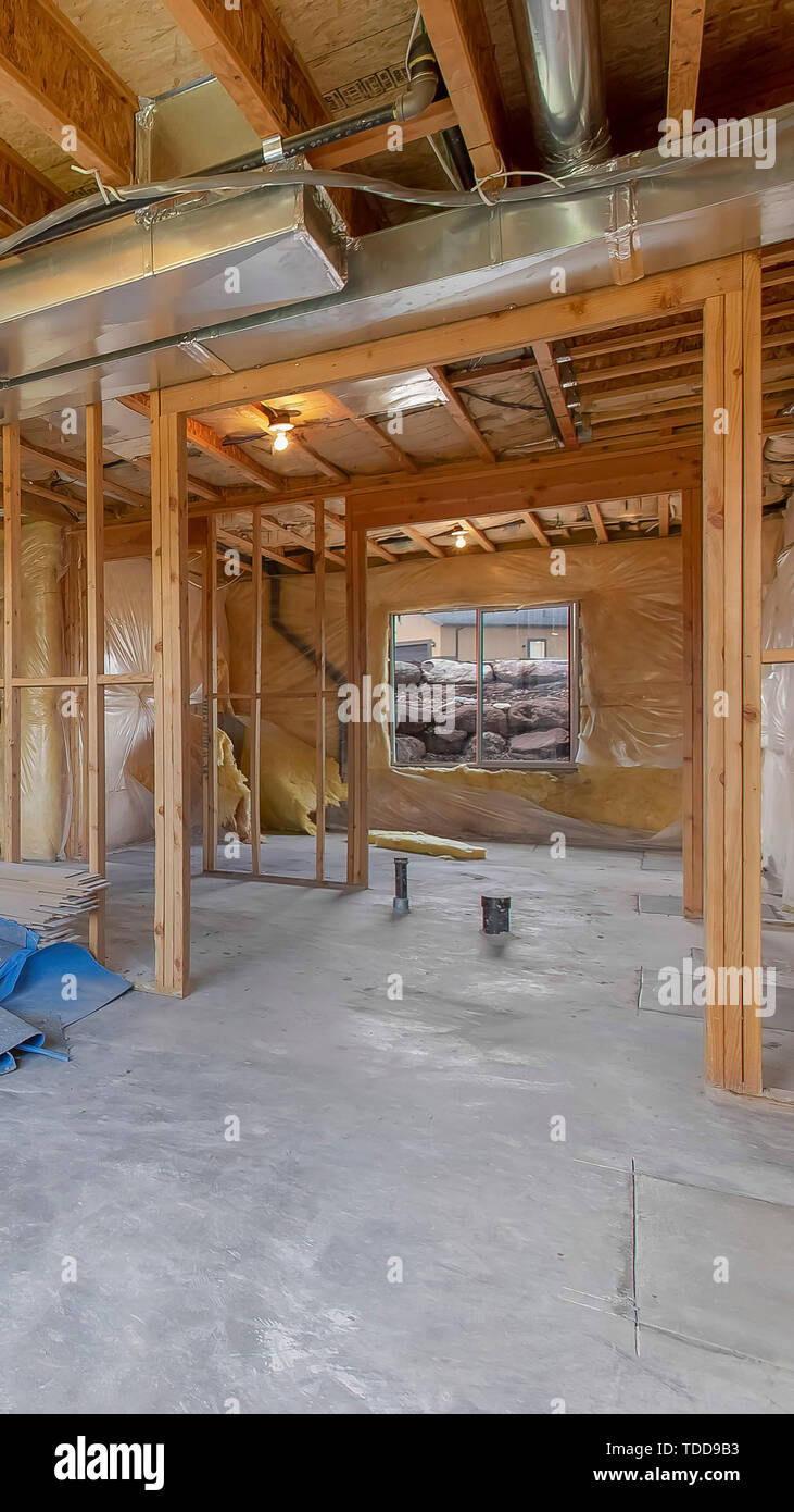Vertical House interior under construction with air conditioning ducts on the ceiling. Walls and window framework can also be seen inside the unfinish Stock Photo