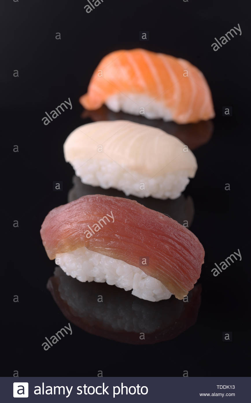 ordered sushi in column on black mirror background - Stock Image