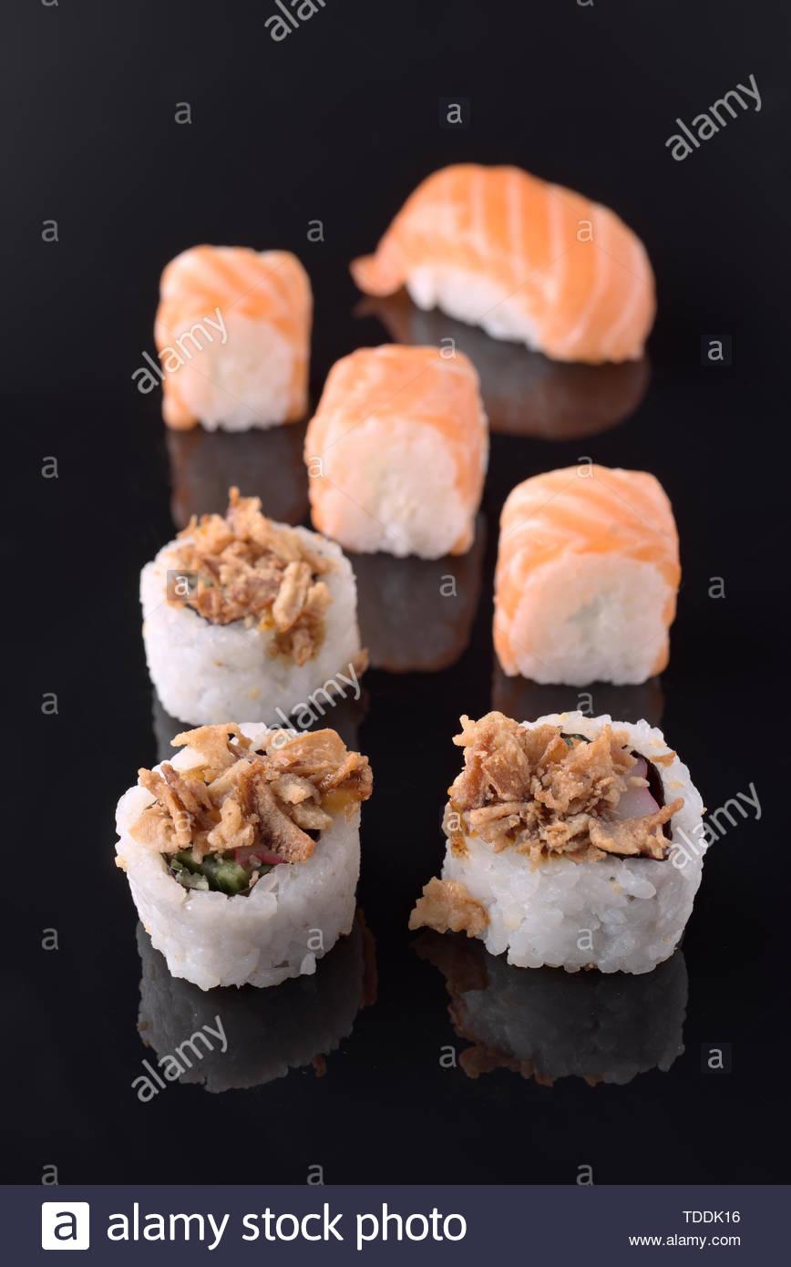 ordered sushi on black mirror background - Stock Image