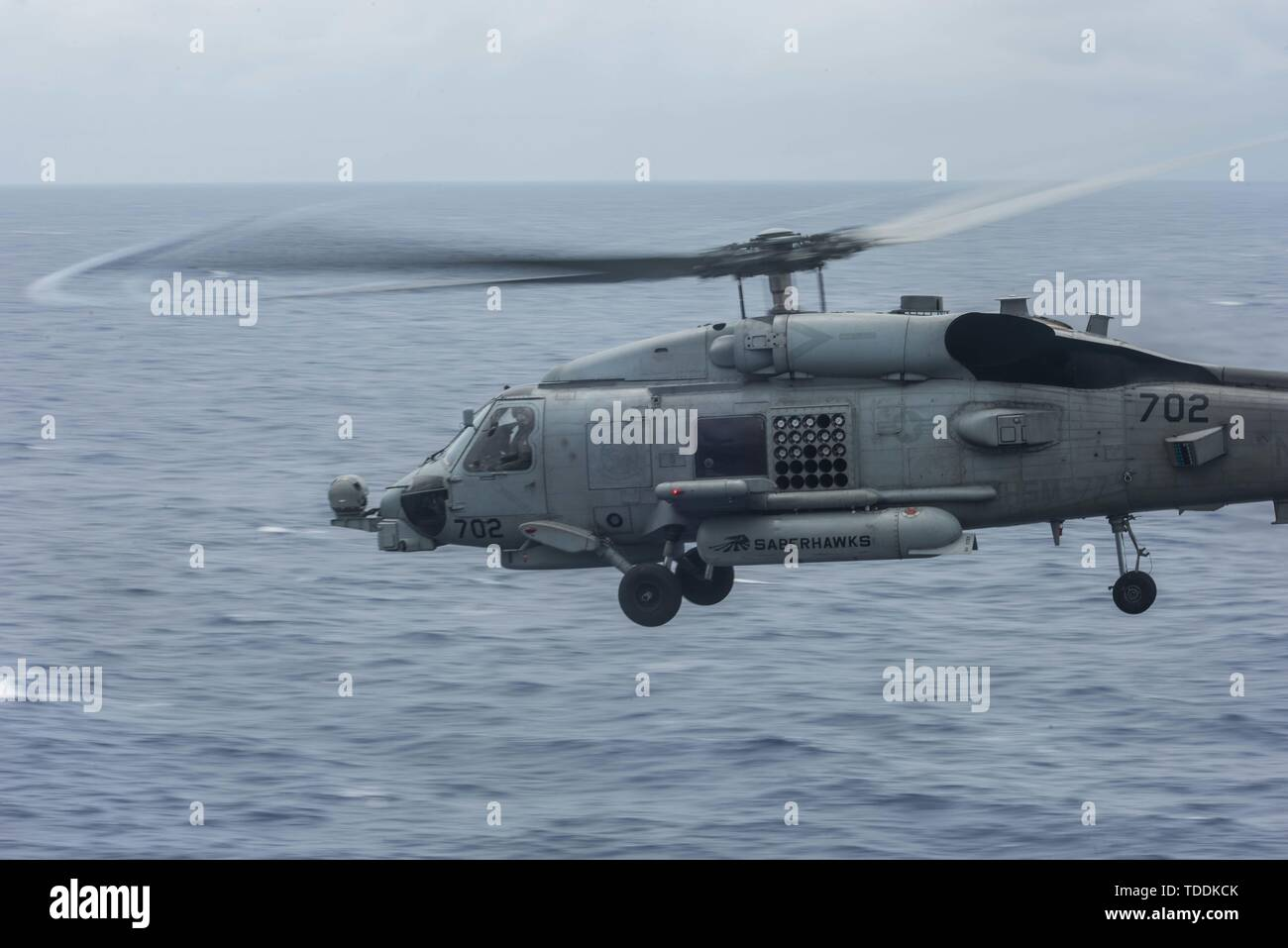190613-N-ZF088-0003 SOUTH CHINA SEA (June 13, 2019) An MH-60R Sea Hawk of Helicopter Maritime Strike Squadron (HSM) 77 flies beside the Navy's forward-deployed aircraft carrier USS Ronald Reagan (CVN 76) during flight deck operations. Ronald Reagan, the flagship of Carrier Strike Group 5, provides a combat-ready force that protects and defends the collective maritime interests of its allies and partners in the Indo-Pacific region. (U.S. Navy photo by Mass Communication Specialist Seaman Gabriel A. Martinez/Released) - Stock Image
