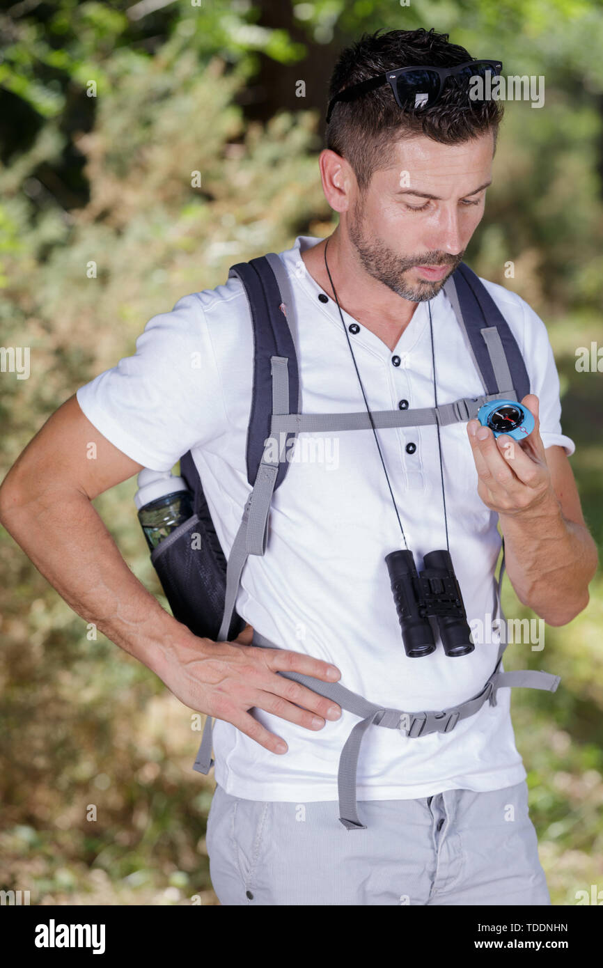 male rambler looking at compass - Stock Image