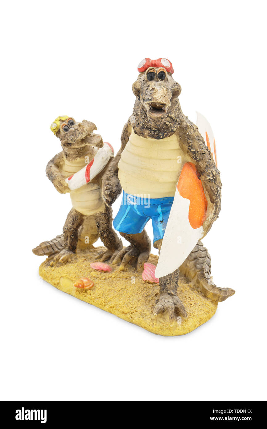 Statuette of two crocodiles on the sandy beach. Isolated on white background. Concept for summer vacation, beach, swimming, surfing. - Stock Image