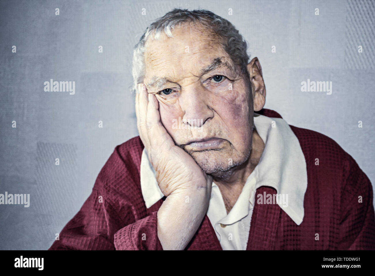Portrait of an elderly man with face closed by hands on black - Stock Image