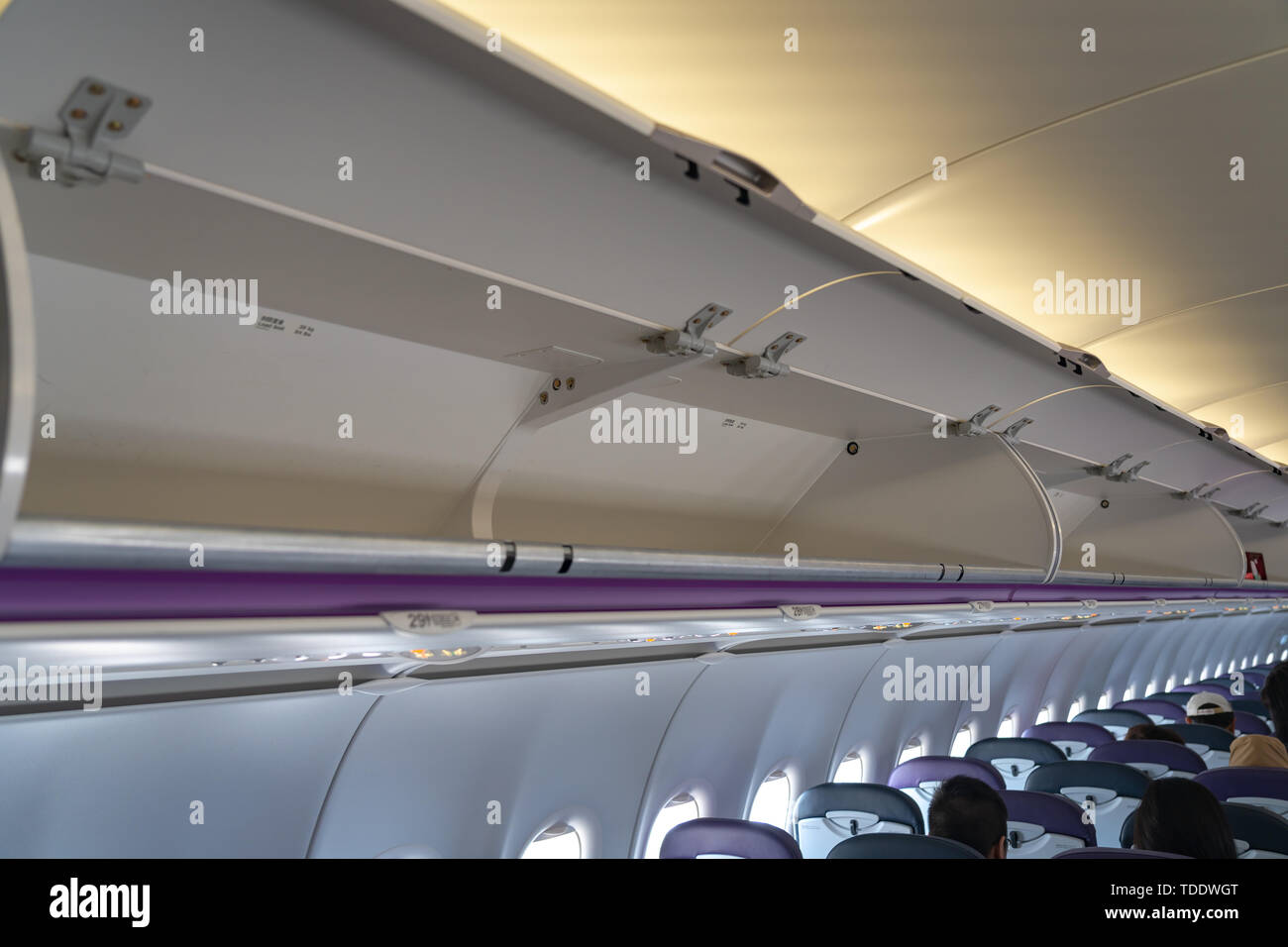 Carry-on luggage in overhead storage compartment on commercial airplane. detail shot of an airplane cabin interior. Travel concept with copy space - Stock Image