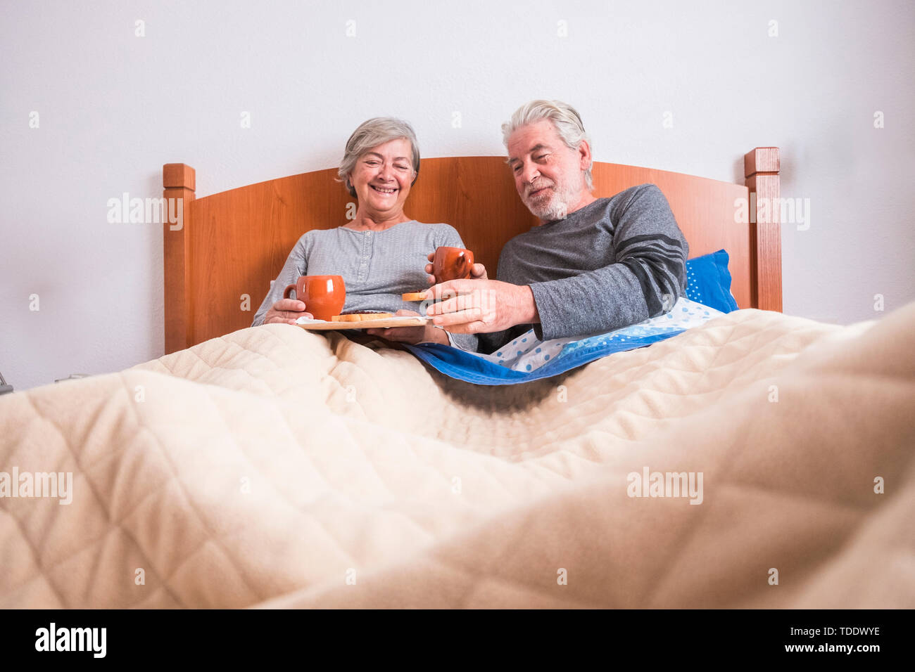 caucasian aged couple doing breakfast at home in the bed. nice natural scene at home for togheterness life concept. love and carefree people married. Stock Photo