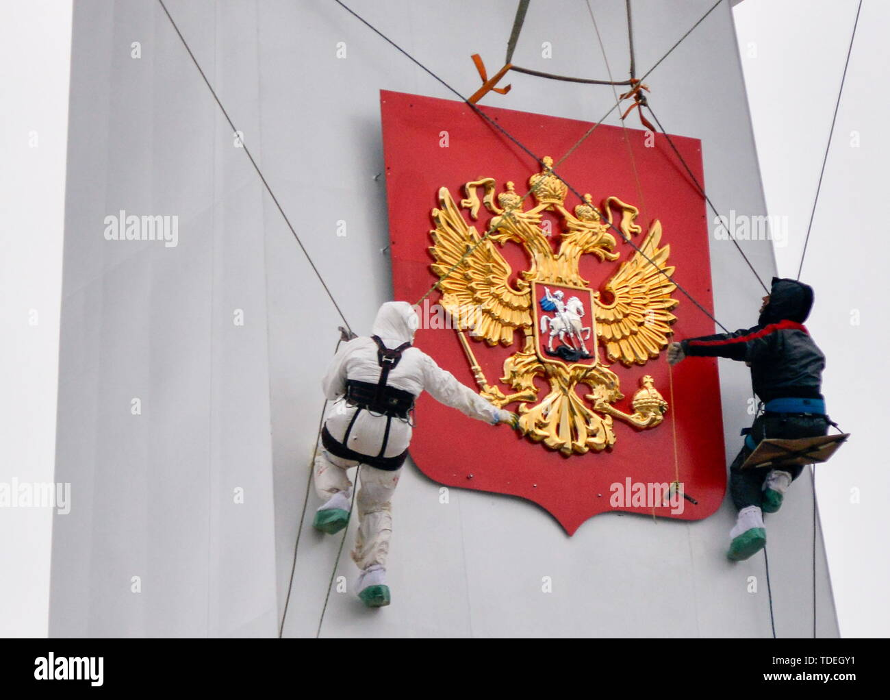 MURMANSK, RUSSIA - JUNE 14, 2019: Workers raise a state emblem banner aboard Akademik Lomonosov, a floating nuclear power unit; being part of a floating nuclear power station, the vessel belongs to a new class of energy sources based on Russian nuclear shipbuilding technologies. Lev Fedoseyev/TASS - Stock Image