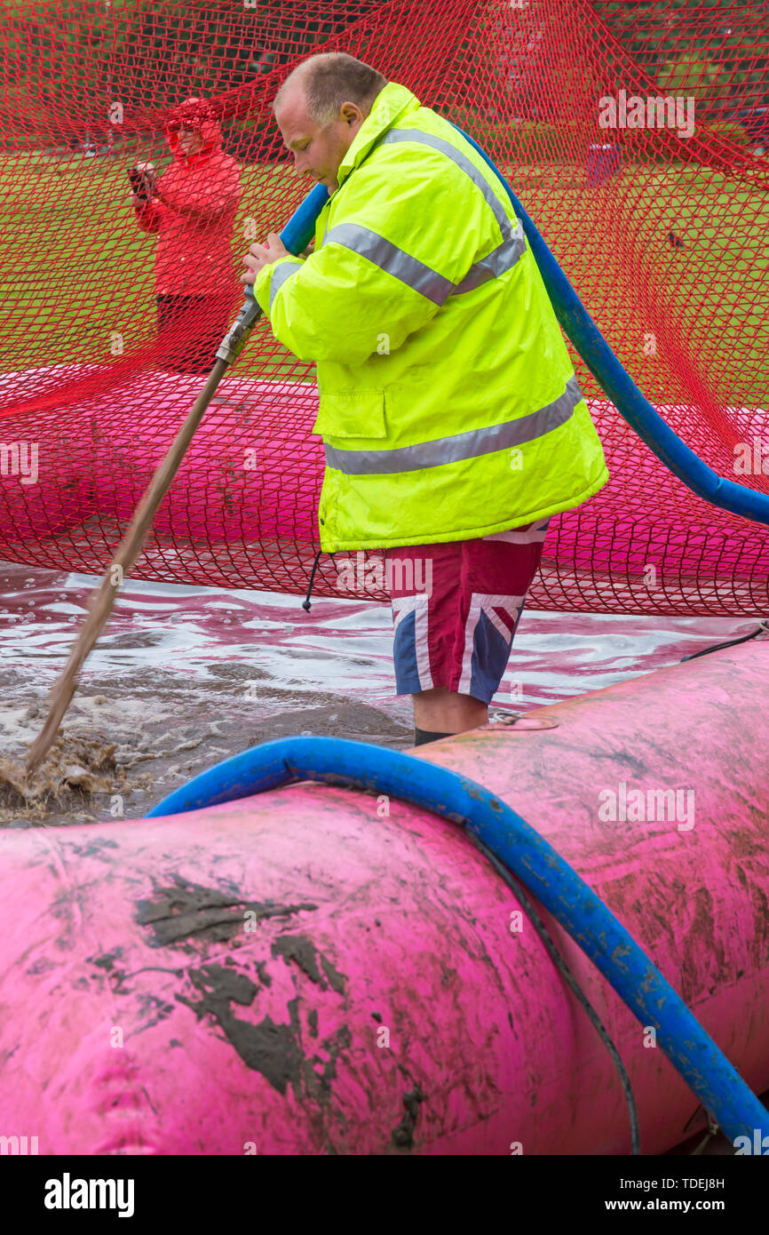 Baiter Park, Poole, Dorset, UK. 15th June 2019. Cold wet day for Race for Life Pretty Muddy. Preparing the mud pool to ensure participants get covered in mud glorious mud! Filling with hose. Credit: Carolyn Jenkins/Alamy Live News - Stock Image
