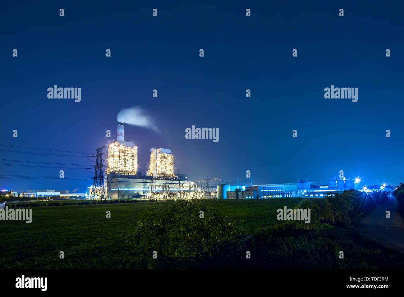 thermal power station near a high way road at nignt - Stock Image