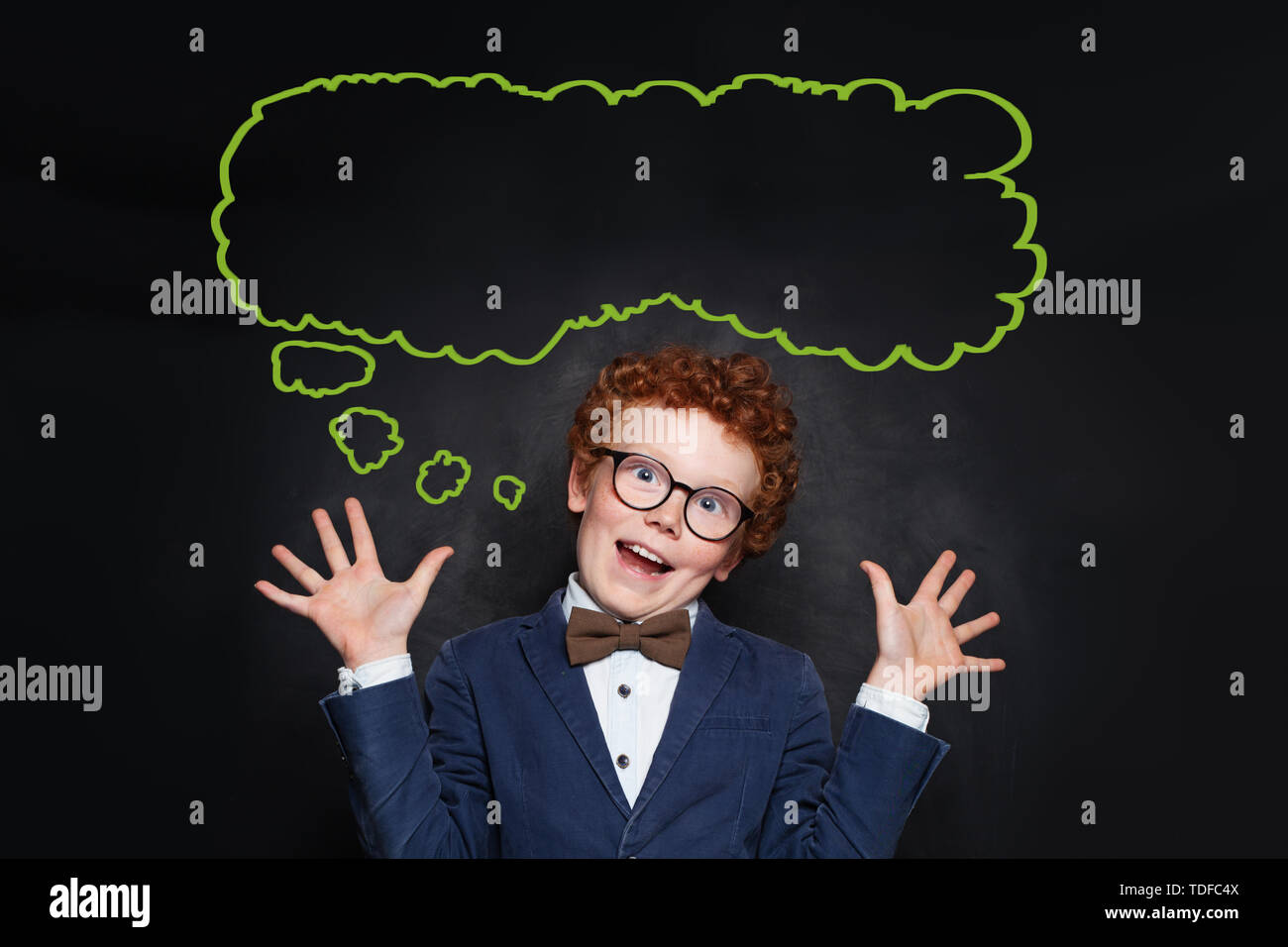 Funny mischievous child boy and empty speech clouds bubbles on chalkboard background Stock Photo