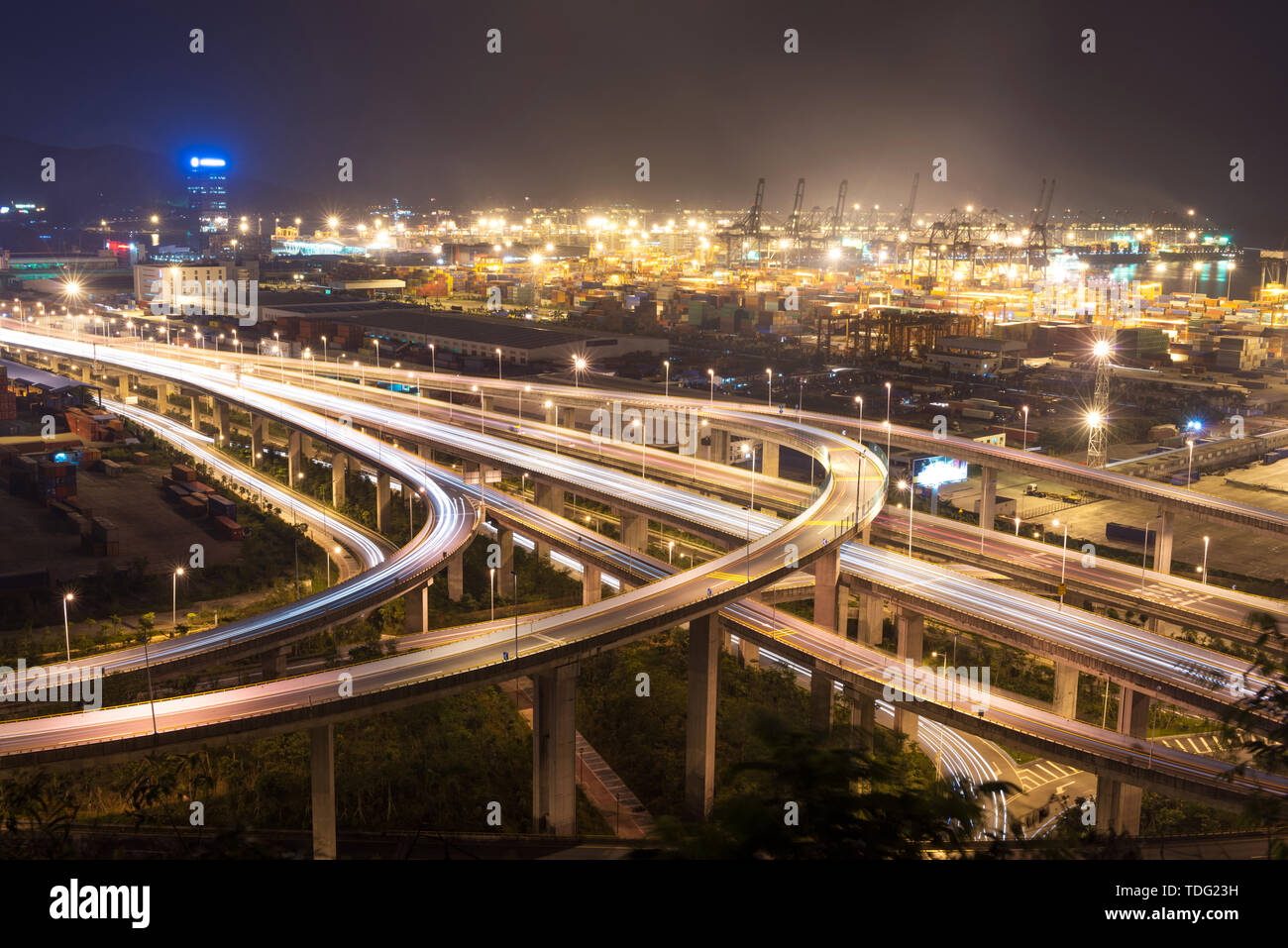 Illuminated and elevated expressway and cityscape at night - Stock Image