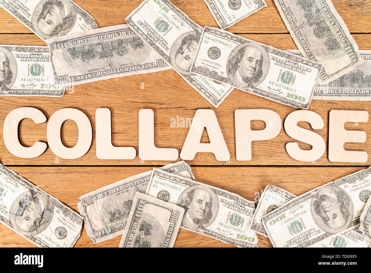word collapse laid out of wooden letters on an old wooden table next to crumpled dollars - Stock Image