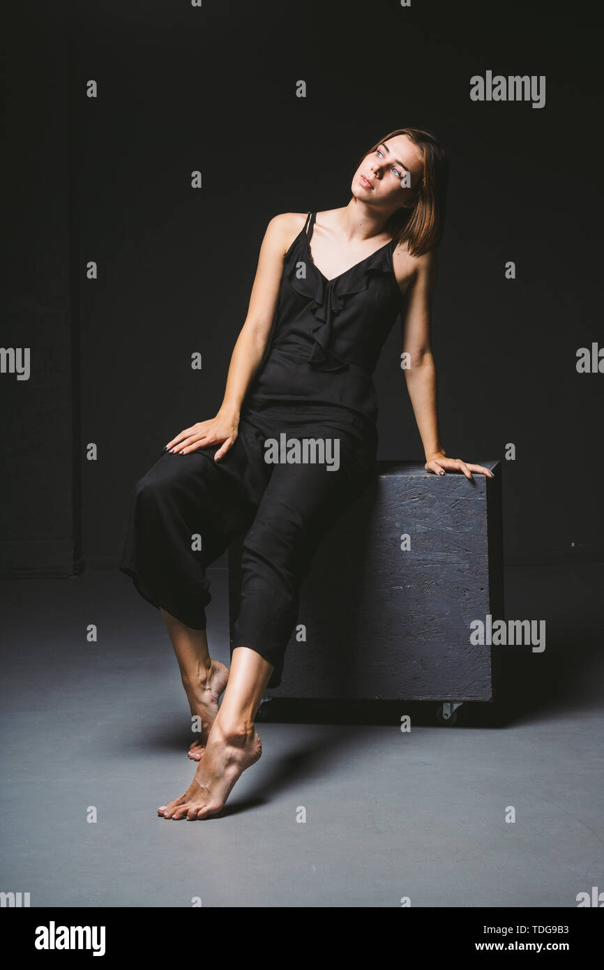 Young Caucasian female model posing in studio black background.Girl sitting in a black dress on a dark wall. Subject severe poor psychological state,  - Stock Image