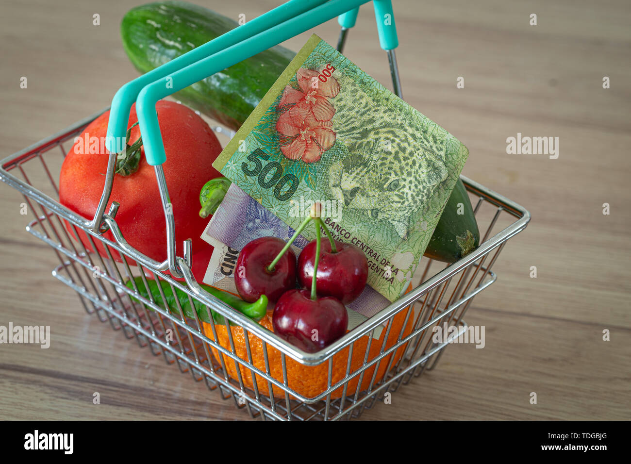vegetables and fruits in the shopping basket along with Argentinean money / the concept of food price increase - Stock Image