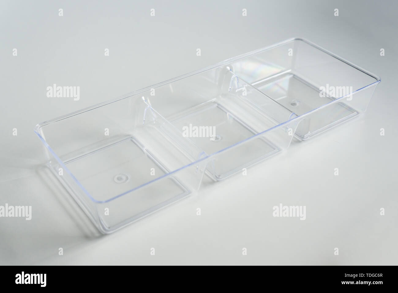 Acrylic clear plastic organizer with 3 square compartments on a white background with empty room space for copy or text. Dividers made of see through  - Stock Image