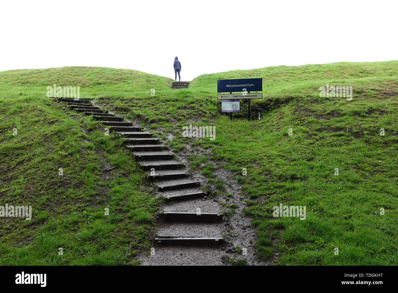 A person stands atop the staircase leading to the Mount Sandel Fort earthen ruins on a rainy day. The exact purpose of the earthwork remains unknown. - Stock Image