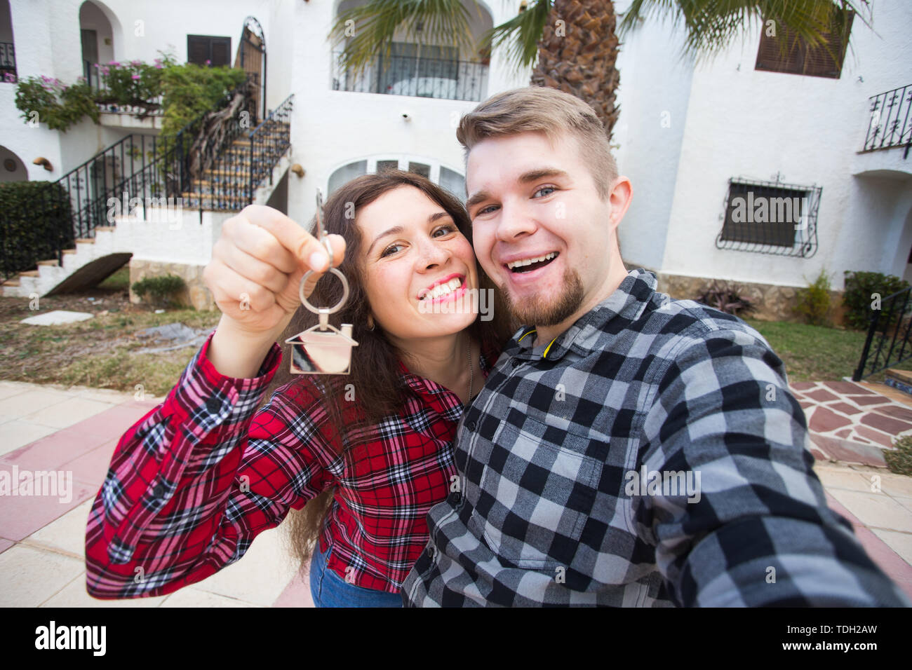 Real estate and property concept - Happy couple holding keys to new home and house miniature - Stock Image