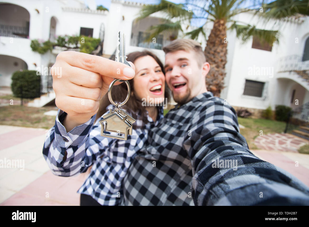 Property, real estate and apartment concept - Happy funny young couple showing a keys of their new house - Stock Image