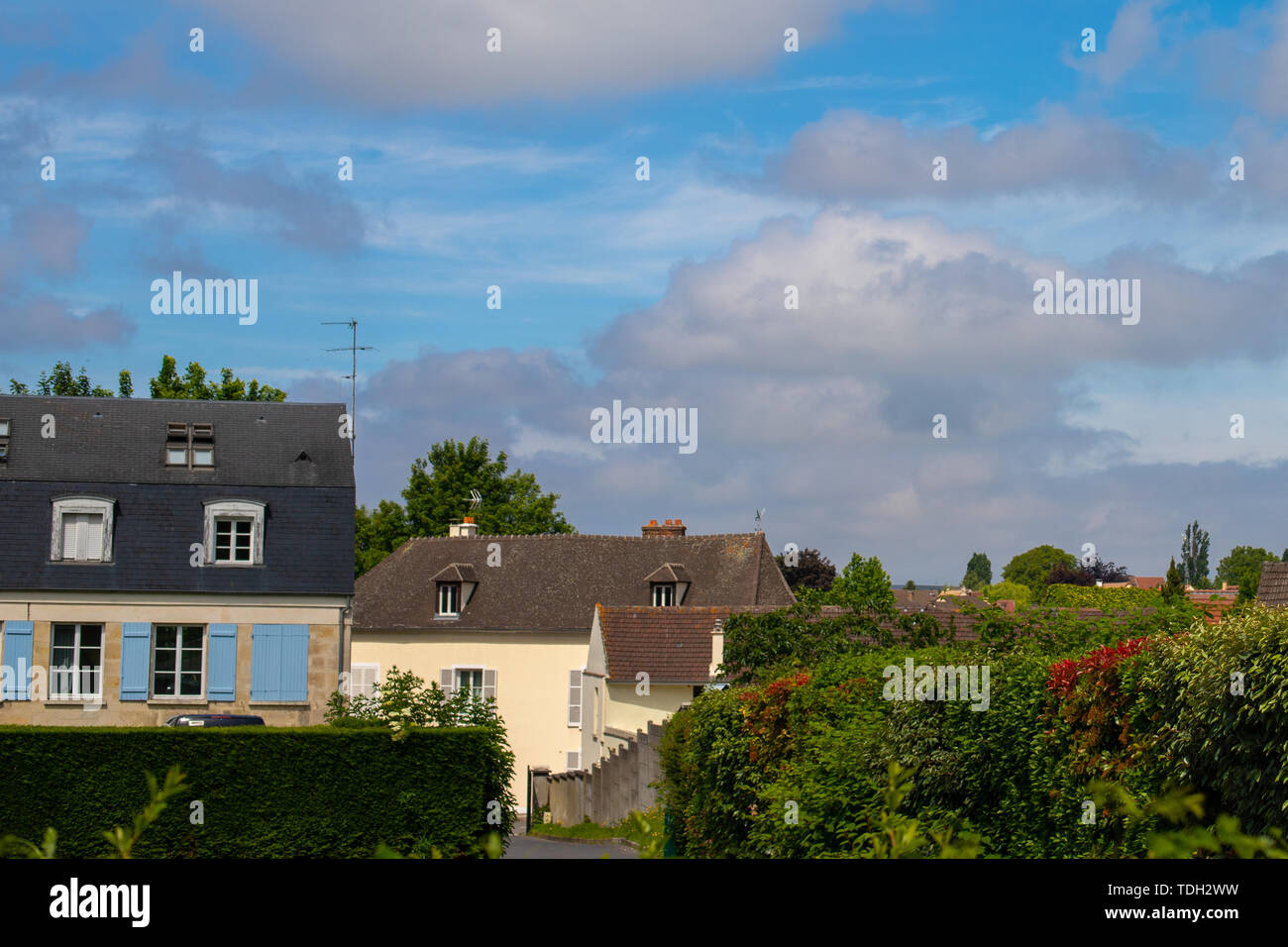 Blue cloudy and contrasting sky over a European village. French country houses. Hedge and lots of greenery down the alley. - Stock Image