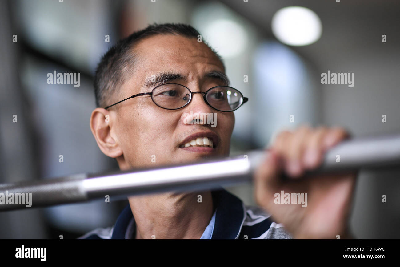 (190616) -- CHENGDU, June 16, 2019 (Xinhua) -- Guan Yongkang adjusts gym equipment for his son in Jinjiang District, Chengdu City, southwest China's Sichuan Province, June 11, 2019. Sun Hongwei, the son of 59-year-old Guan Yongkang, was born with cerebral palsy in 1995 and suffered from amyotrophy.  Sun ever received professional rehabilitation training in training courses organized by Chengdu Qingyang Federation of Disabled Persons in 2004. Later he stopped the course because of overage. In 2015, his father Guan decided to take him to practice in the gym. After a period of searching, a gym ac - Stock Image