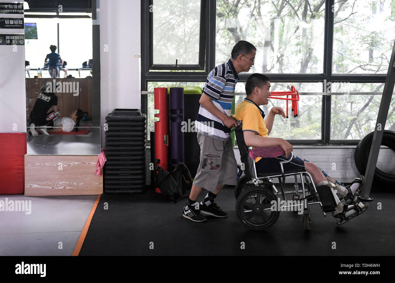 (190616) -- CHENGDU, June 16, 2019 (Xinhua) -- Guan Yongkang and his son prepare to pratice at the gym in Jinjiang District, Chengdu City, southwest China's Sichuan Province, June 11, 2019. Sun Hongwei, the son of 59-year-old Guan Yongkang, was born with cerebral palsy in 1995 and suffered from amyotrophy.  Sun ever received professional rehabilitation training in training courses organized by Chengdu Qingyang Federation of Disabled Persons in 2004. Later he stopped the course because of overage. In 2015, his father Guan decided to take him to practice in the gym. After a period of searching,  - Stock Image