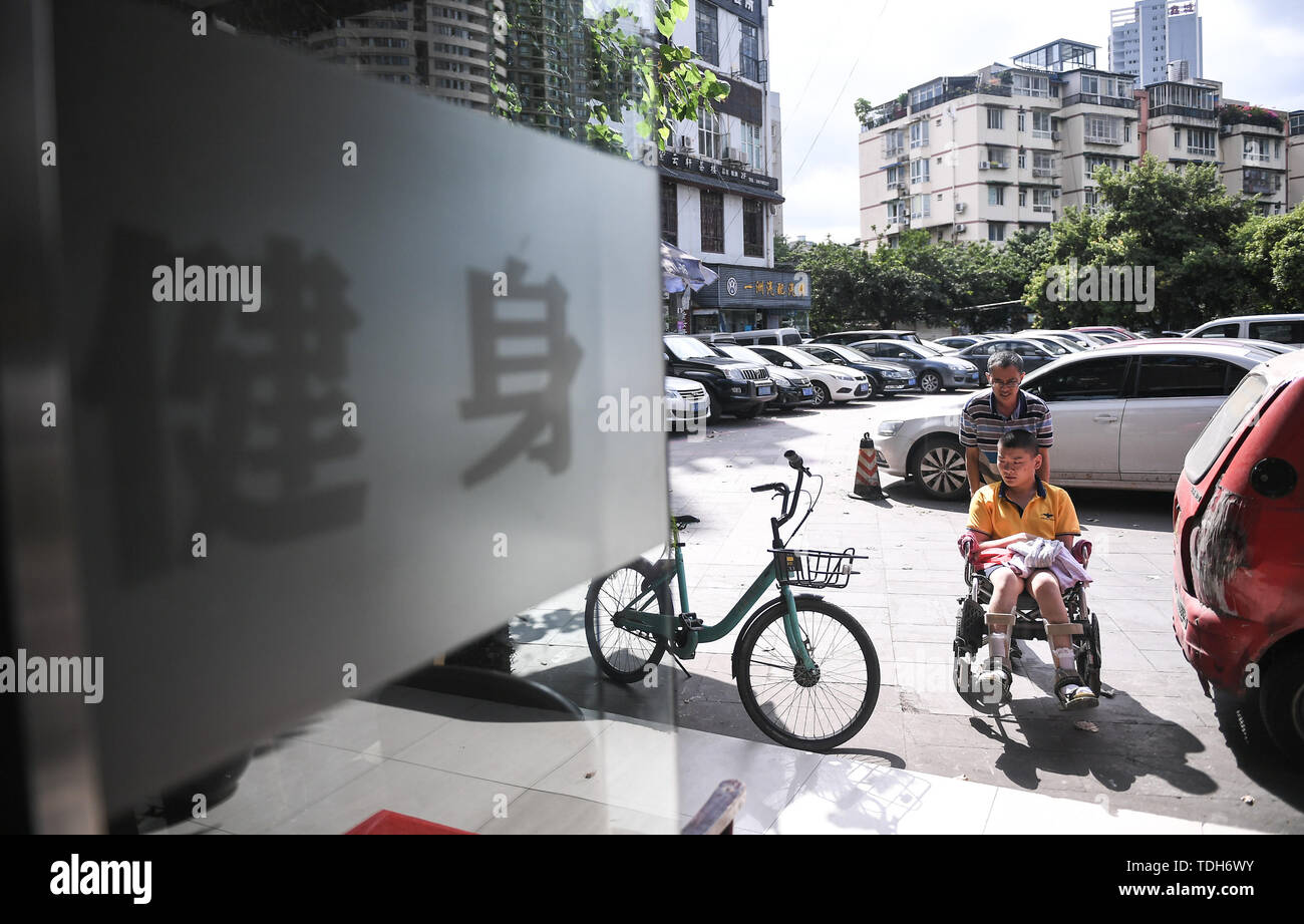(190616) -- CHENGDU, June 16, 2019 (Xinhua) -- Guan Yongkang and his son go into the gym in Jinjiang District, Chengdu City, southwest China's Sichuan Province, June 11, 2019. Sun Hongwei, the son of 59-year-old Guan Yongkang, was born with cerebral palsy in 1995 and suffered from amyotrophy.  Sun ever received professional rehabilitation training in training courses organized by Chengdu Qingyang Federation of Disabled Persons in 2004. Later he stopped the course because of overage. In 2015, his father Guan decided to take him to practice in the gym. After a period of searching, a gym accepted - Stock Image
