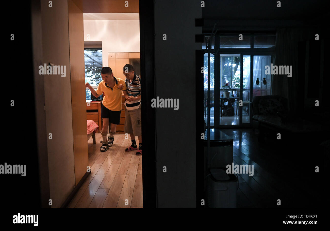 (190616) -- CHENGDU, June 16, 2019 (Xinhua) -- Guan Yongkang helps his son to go washing after they getting up in Jinjiang District, Chengdu City, southwest China's Sichuan Province, June 11, 2019. Sun Hongwei, the son of 59-year-old Guan Yongkang, was born with cerebral palsy in 1995 and suffered from amyotrophy.  Sun ever received professional rehabilitation training in training courses organized by Chengdu Qingyang Federation of Disabled Persons in 2004. Later he stopped the course because of overage. In 2015, his father Guan decided to take him to practice in the gym. After a period of sea - Stock Image