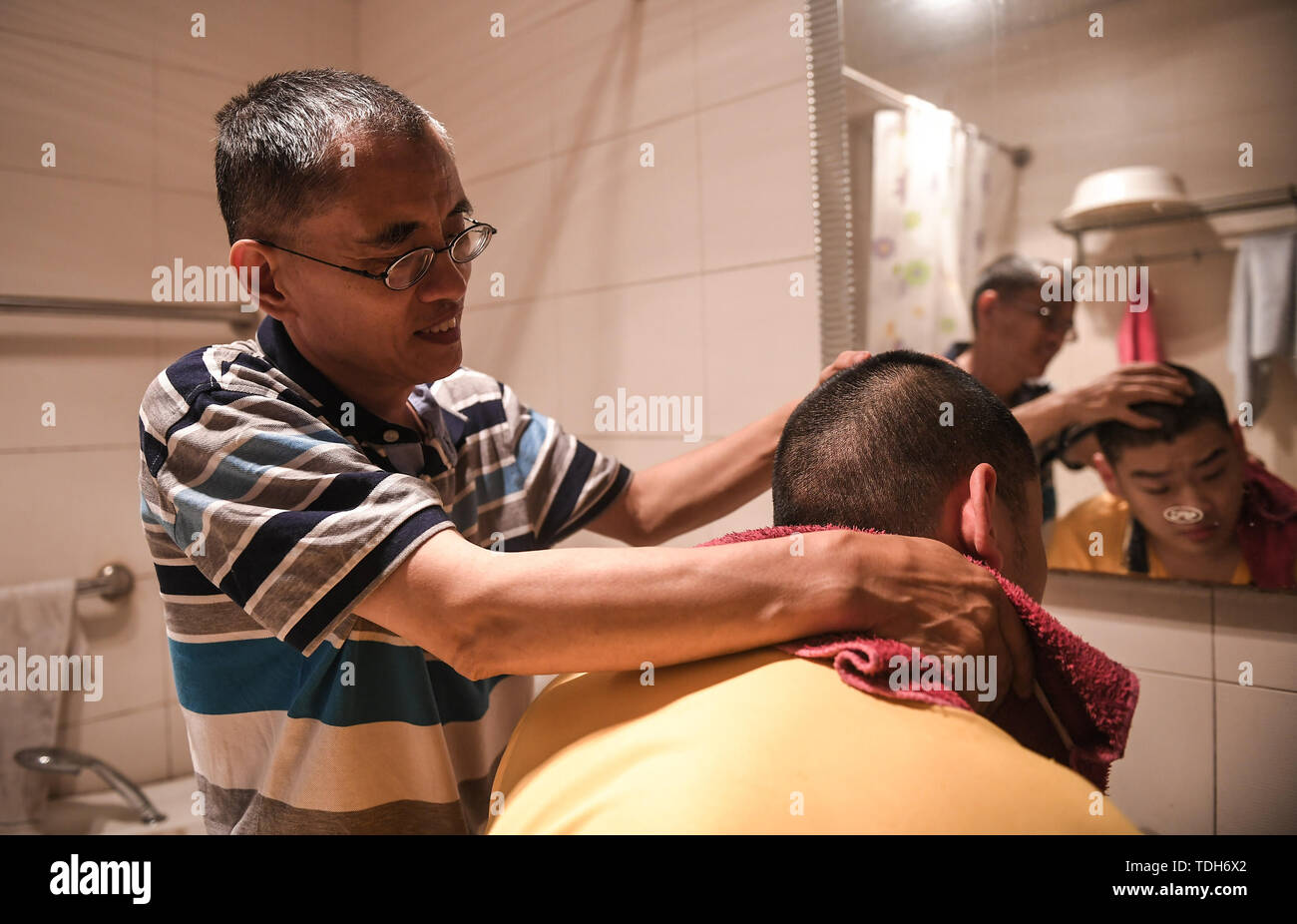 (190616) -- CHENGDU, June 16, 2019 (Xinhua) -- Guan Yongkang helps his son to wash face in Jinjiang District, Chengdu City, southwest China's Sichuan Province, June 11, 2019. Sun Hongwei, the son of 59-year-old Guan Yongkang, was born with cerebral palsy in 1995 and suffered from amyotrophy.  Sun ever received professional rehabilitation training in training courses organized by Chengdu Qingyang Federation of Disabled Persons in 2004. Later he stopped the course because of overage. In 2015, his father Guan decided to take him to practice in the gym. After a period of searching, a gym accepted  - Stock Image