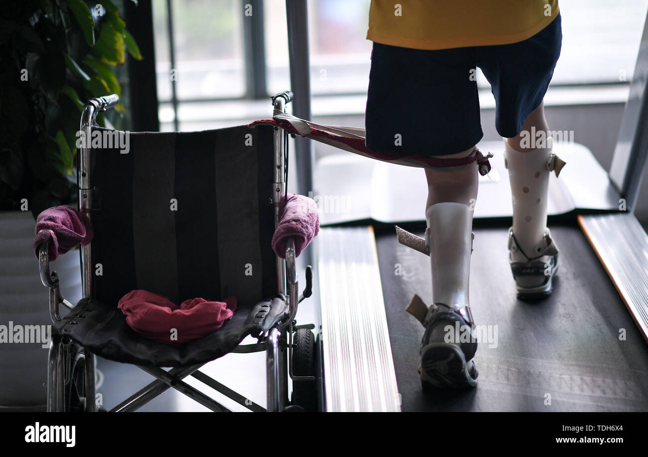 (190616) -- CHENGDU, June 16, 2019 (Xinhua) -- Sun Hongwei exercises on a treadmill at the gym in Jinjiang District, Chengdu City, southwest China's Sichuan Province, June 11, 2019. Sun Hongwei, the son of 59-year-old Guan Yongkang, was born with cerebral palsy in 1995 and suffered from amyotrophy.  Sun ever received professional rehabilitation training in training courses organized by Chengdu Qingyang Federation of Disabled Persons in 2004. Later he stopped the course because of overage. In 2015, his father Guan decided to take him to practice in the gym. After a period of searching, a gym ac - Stock Image