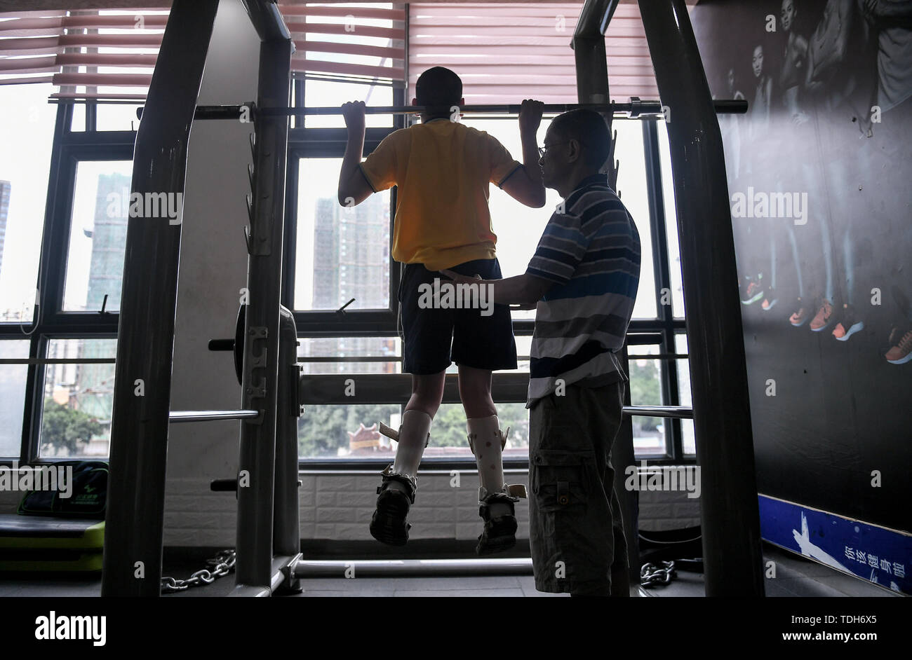 (190616) -- CHENGDU, June 16, 2019 (Xinhua) -- Guan Yongkang helps his son to exercise at the gym in Jinjiang District, Chengdu City, southwest China's Sichuan Province, June 11, 2019. Sun Hongwei, the son of 59-year-old Guan Yongkang, was born with cerebral palsy in 1995 and suffered from amyotrophy.  Sun ever received professional rehabilitation training in training courses organized by Chengdu Qingyang Federation of Disabled Persons in 2004. Later he stopped the course because of overage. In 2015, his father Guan decided to take him to practice in the gym. After a period of searching, a gym - Stock Image