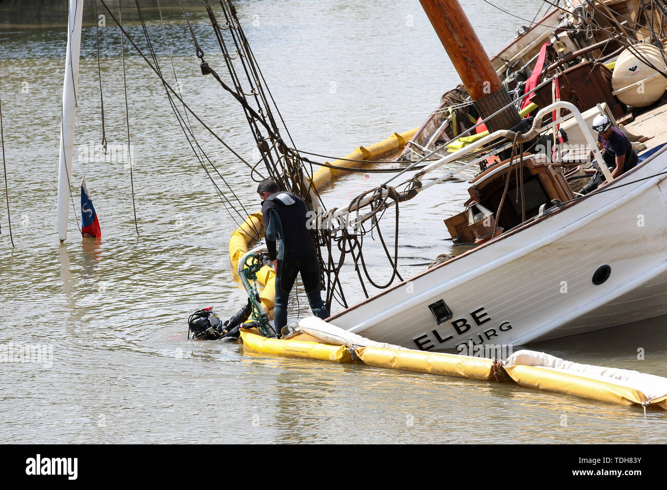 """Stadersand, Germany. 16th June, 2019. Employees of a Spanish company prepare with divers the salvage of the sunken historic sailing ship """"No 5 Elbe"""" in the harbour of Stadersand. The historic sailing ship, which has only recently been extensively renovated, collided with a container ship on the Elbe and sank. Credit: Bodo Marks/dpa/Alamy Live News Stock Photo"""
