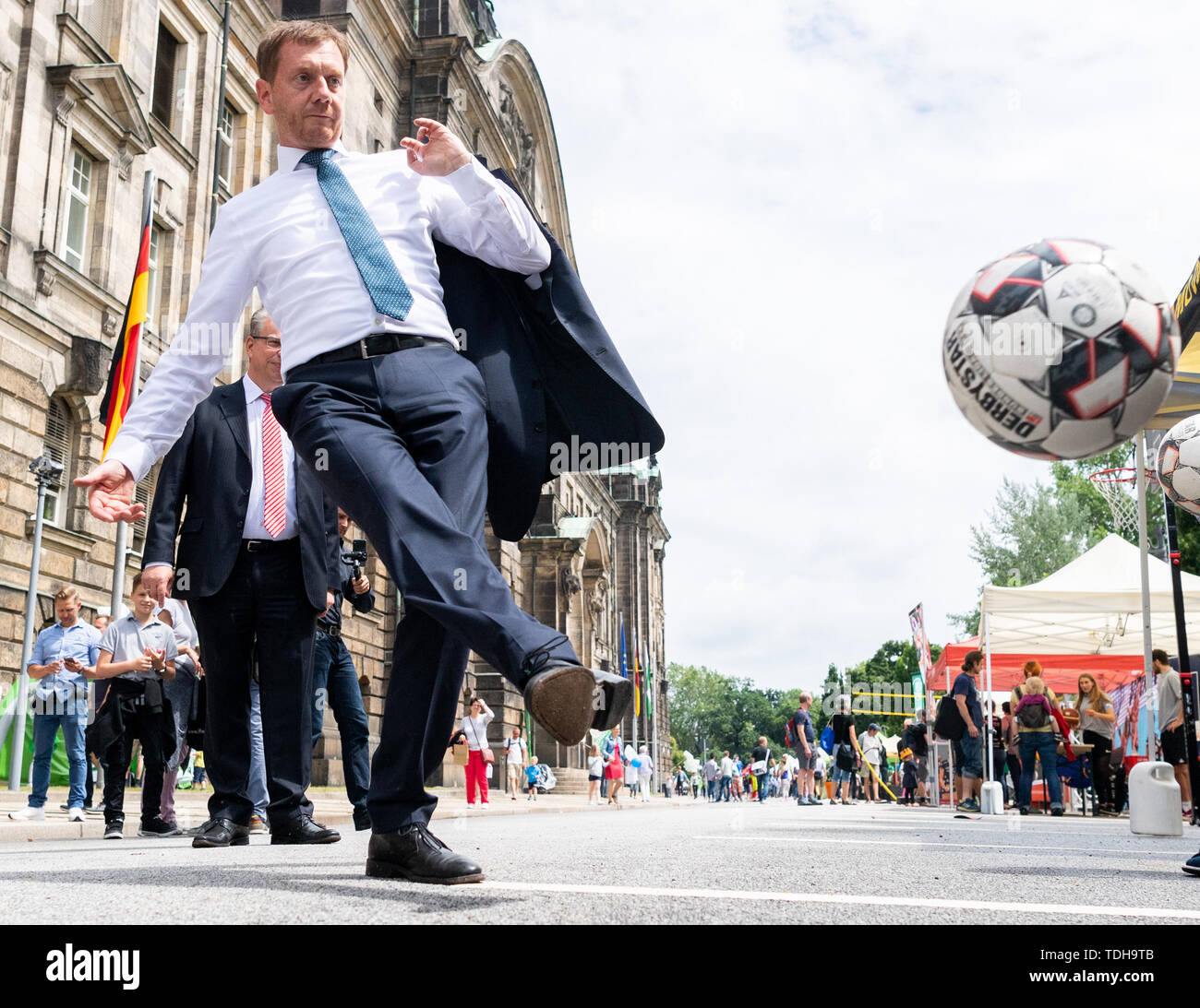 Dresden, Germany. 16th June, 2019. Michael Kretschmer (CDU), Prime Minister of Saxony, plays football in front of the Saxon State Chancellery during the 17th day of the Open Government Quarter. Interested citizens have the opportunity to look behind otherwise closed doors and inform themselves about politics and administration in the Free State. Credit: Robert Michael/dpa-Zentralbild/ZB/dpa/Alamy Live News Stock Photo