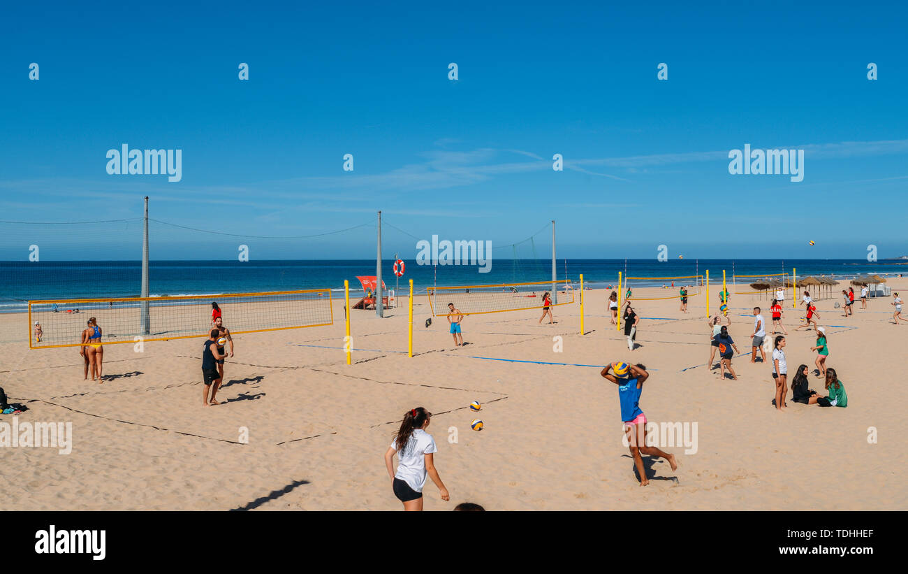 Cascais, Portugal - June 10, 2019: Young women play volleyball on the beach in Carcavelos, Portugal - Stock Image