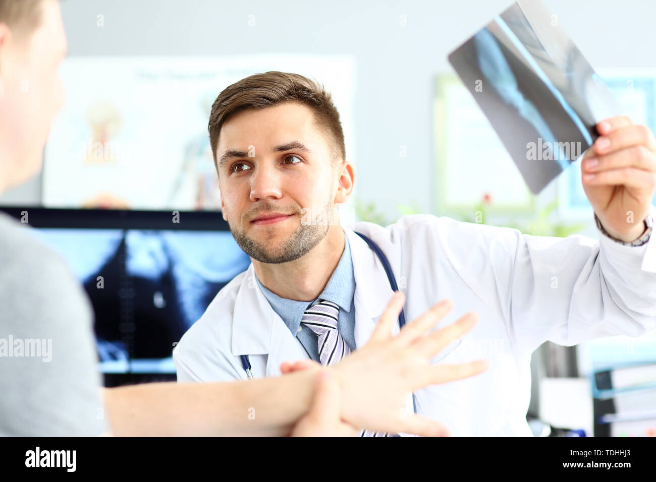 Portrait of smiling doctor talking with patient about good snapshot results. Doc looking at visitor with joyfulness. Medical and healthcare concept. B - Stock Image