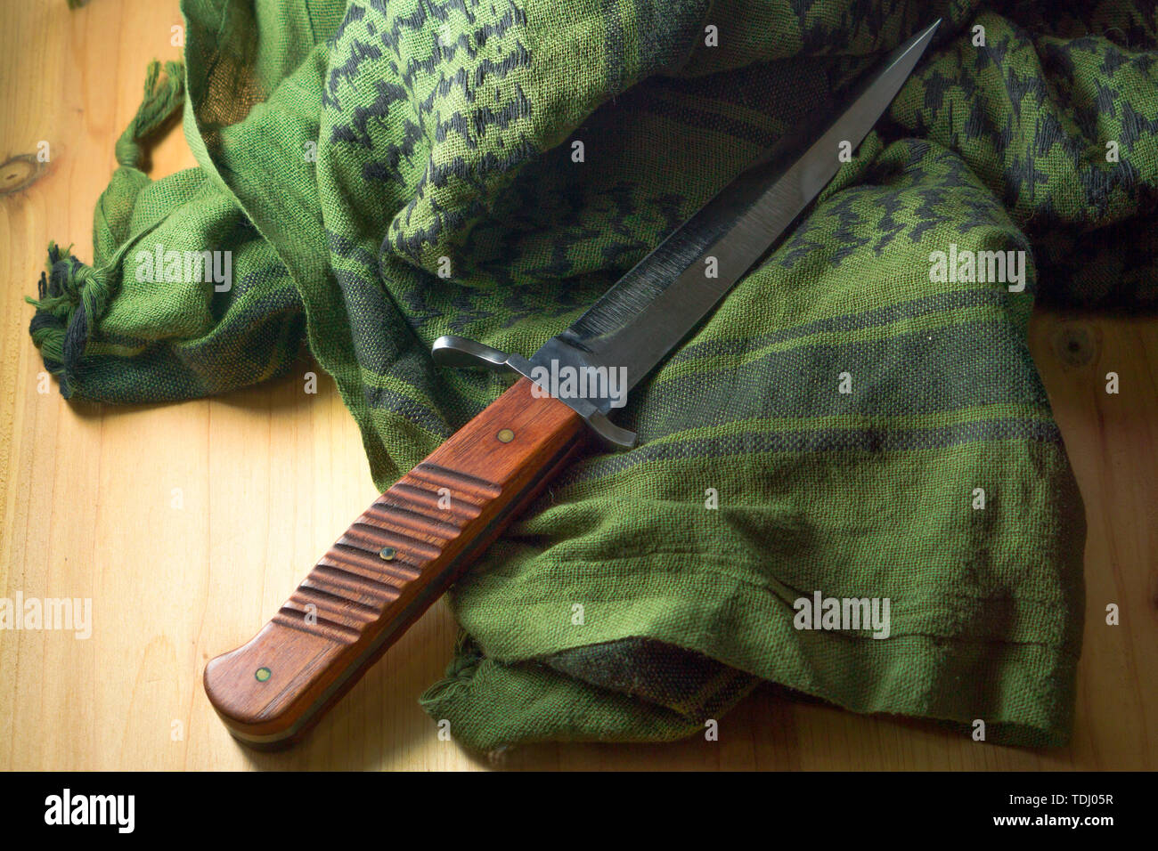 combat knife with a wooden handle, green shemagh - Stock Image