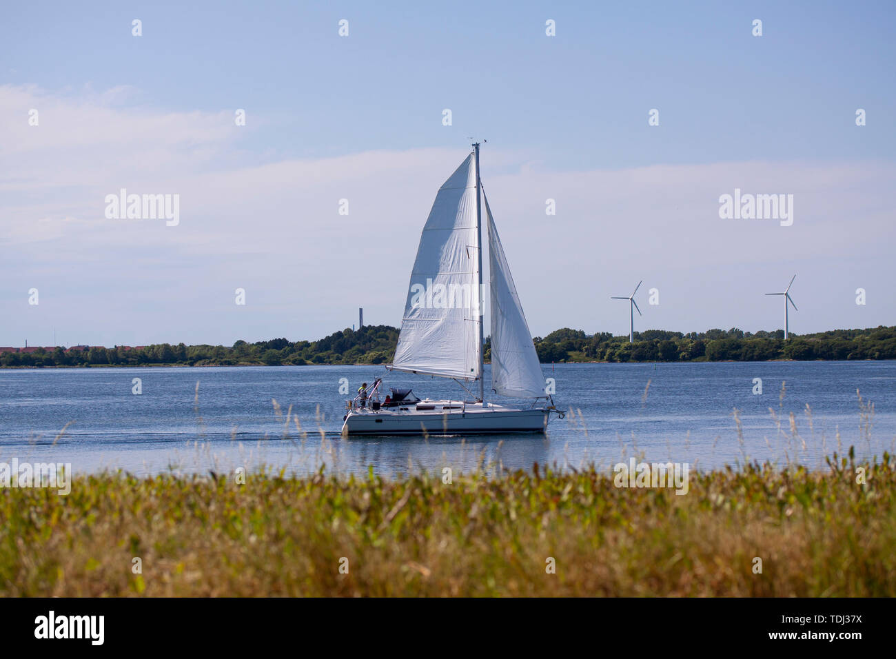 Sailboat for full sail on a river on a sunny day with wind turbines in the background. Copenhagen, Denmark - June 14, 2019. Stock Photo