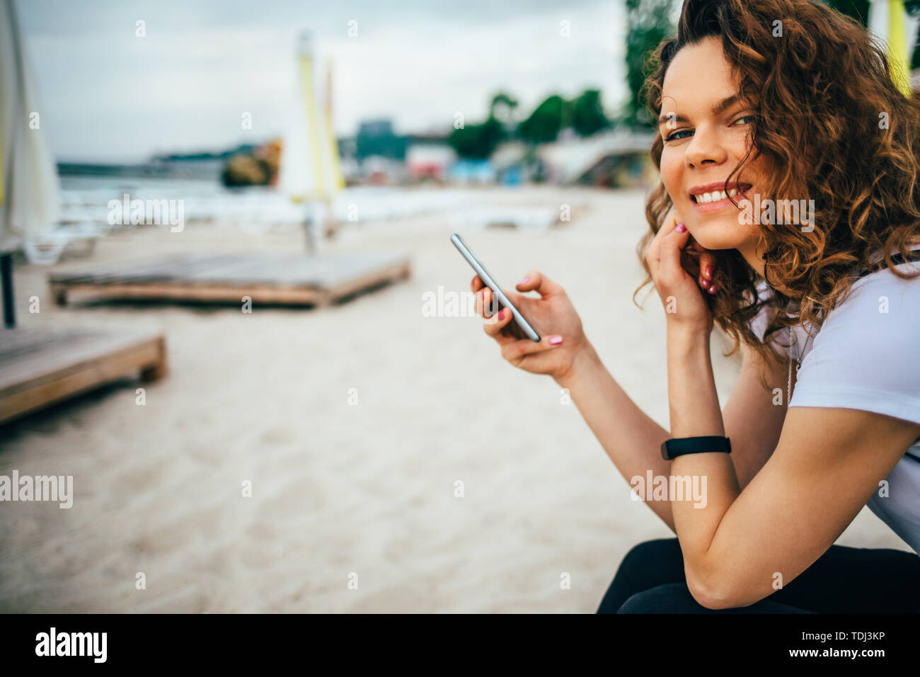 Joyful female using mobile device sitting outdoors on sand  beach near sea folded umbrellas and sun loungers. Cheerful young woman smiling looking at  - Stock Image