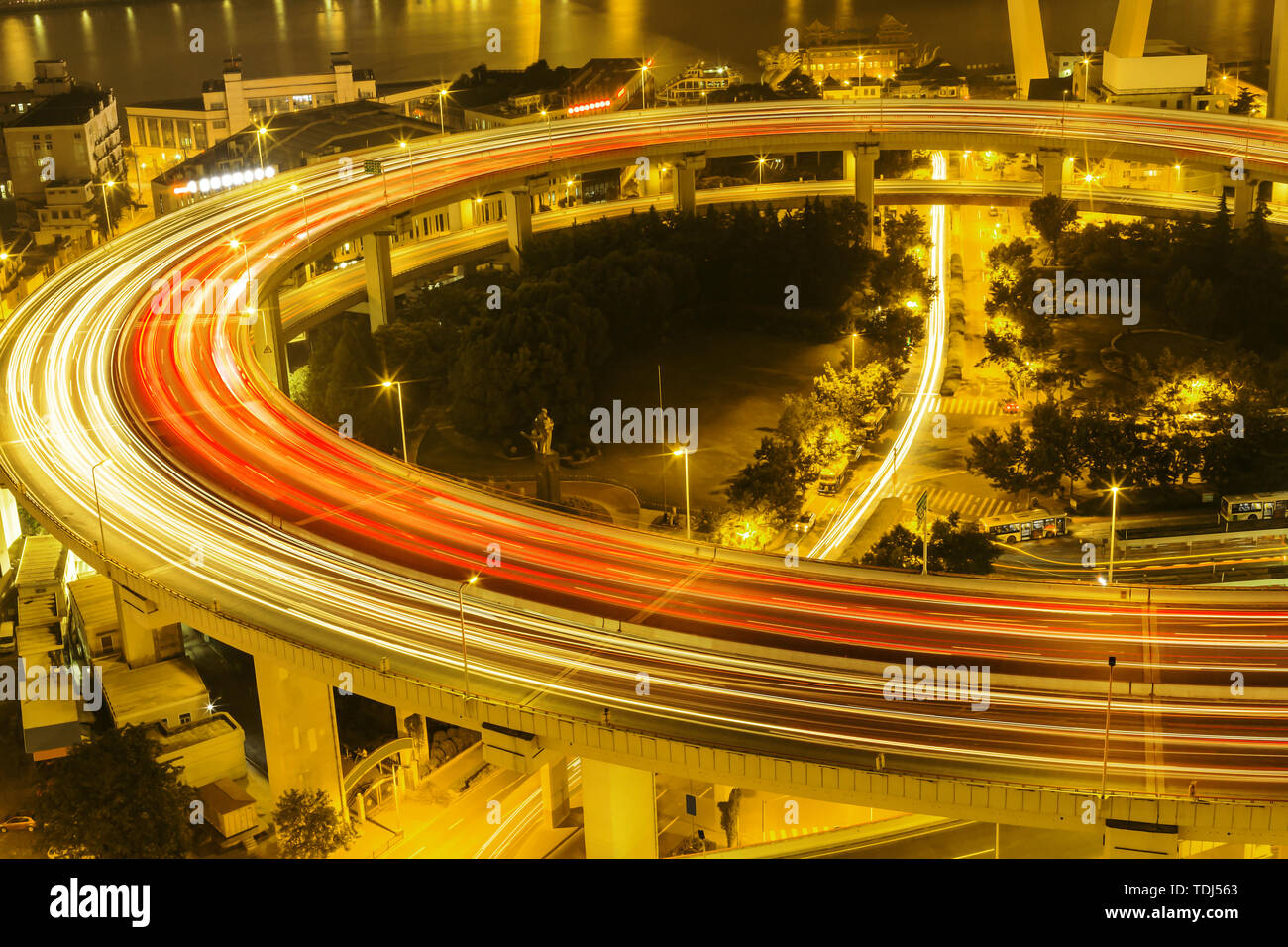 illuminated road intersection and traffic trails - Stock Image