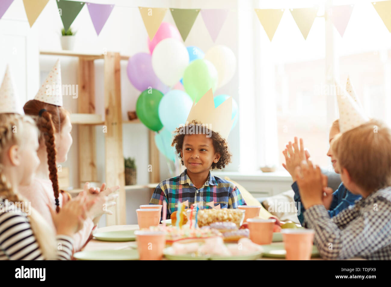 Portrait of smiling African-American boy wearing crown sitting at table while celebrating Birthday with friends, copy space Stock Photo