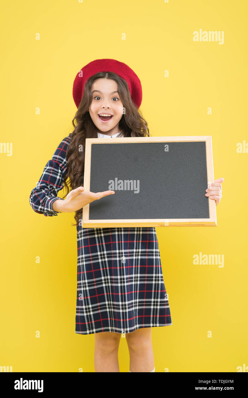 presenting product. small girl in french beret. happy girl with curly hair in beret. advertisement. child with empty blackboard. child on yellow. copy space. school time. presenting school project. Stock Photo