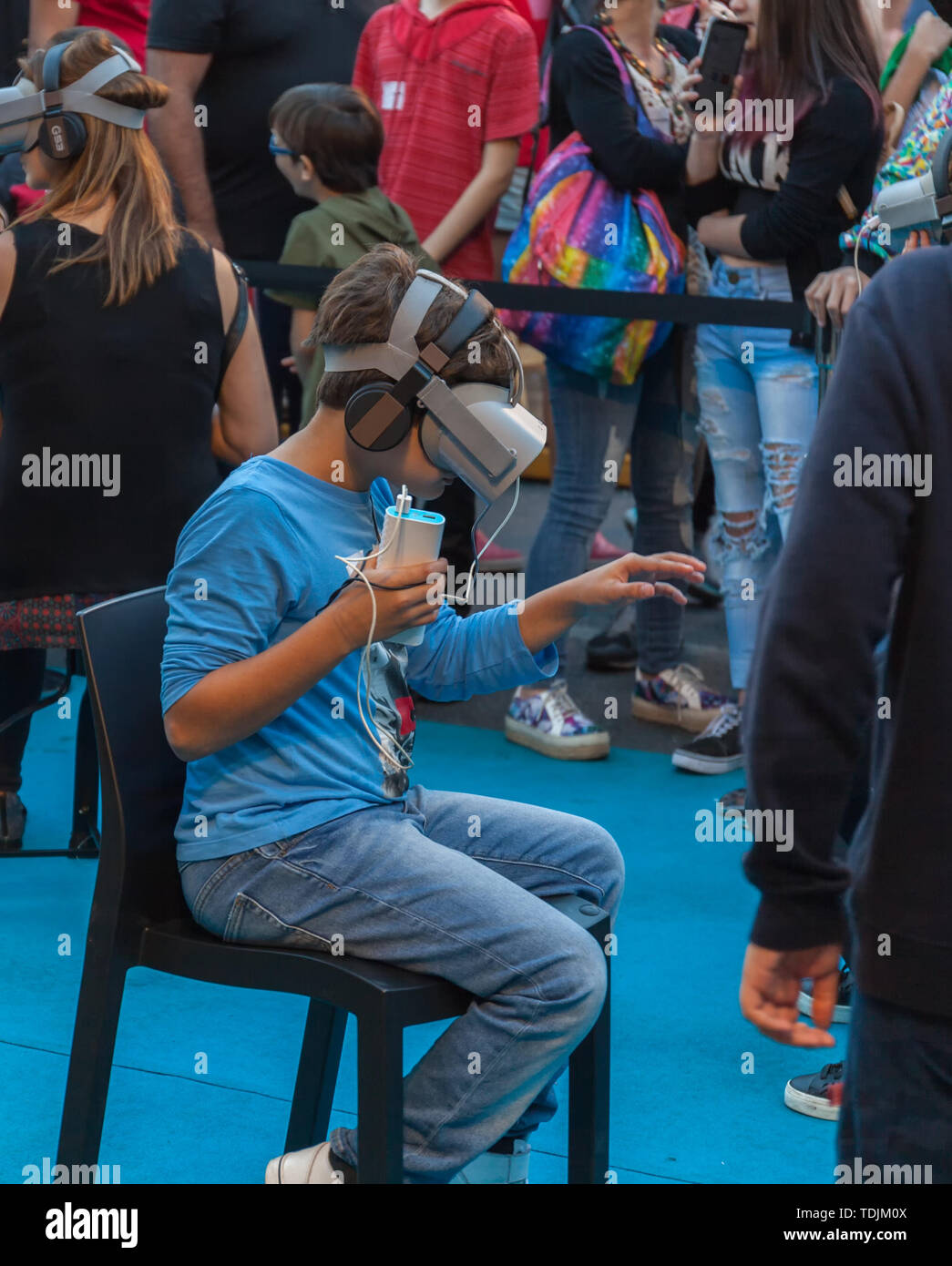 A boy and girl explore the possibilities of virtual reality glasses at a street exhibition, on Santelmo Avenue, Buenos Aires, Argentina. May 15, 2019. - Stock Image
