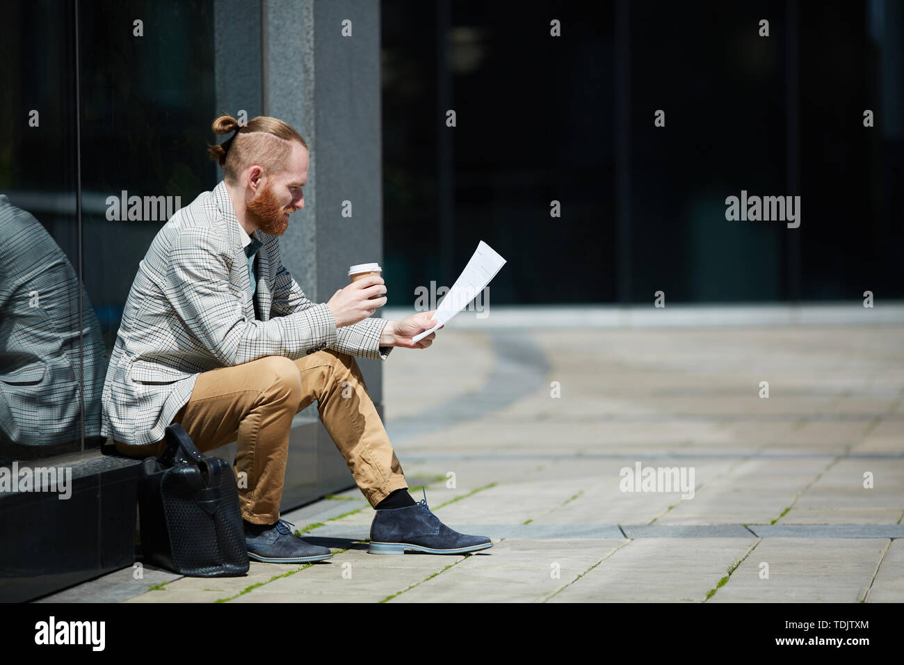 Thoughtful handsome young freelance analyst sitting outdoors and examining data report while drinking coffee - Stock Image