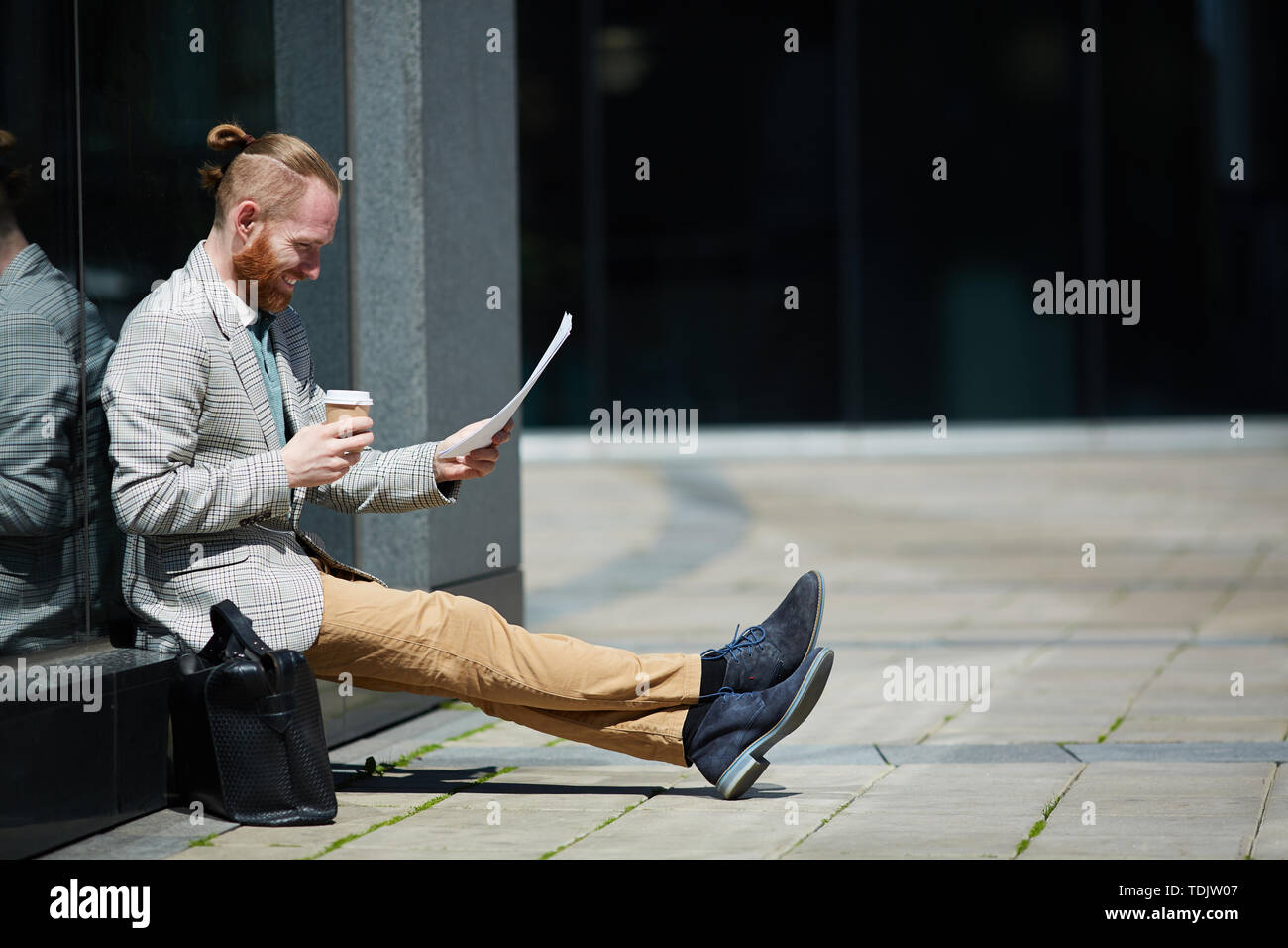 Positive successful hipster young lawyer with beard sitting outdoors and reading papers while preparing for court pleading Stock Photo